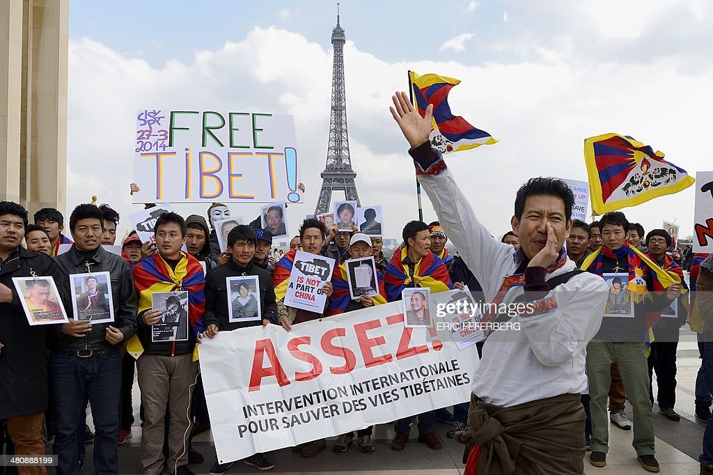 Tibetans living abroad hold Tibetan flags and a banner reading 'Enough We want an international interventions to save the lives of Tibetans' as they...