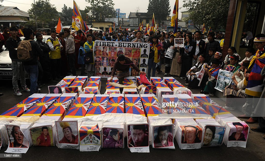 Tibetans offer prayers near mock coffins to represent the victims of selfimmolation during a rally in Siliguri on February 8 2012 China said February...