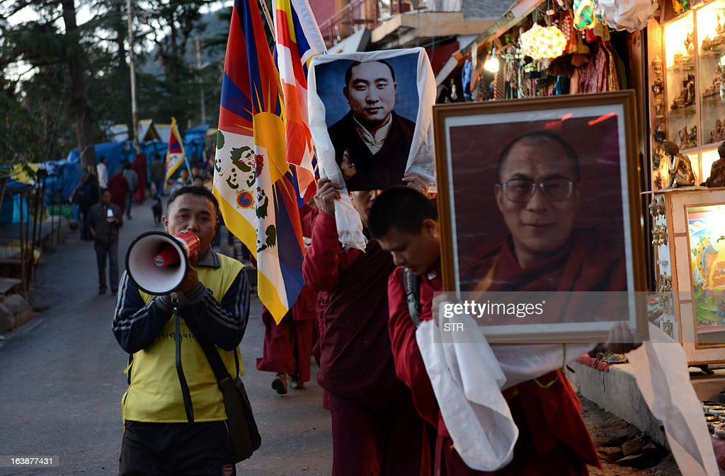 Tibetans-in-exile carry a picture of the Dalai Lama (R) on their way to stage a candlelight vigil to mourn the death of Lobsang Thokmay, a monk of Kirti monastery in Tibet's Amdo region, after he set himself ablaze on March 16 in protest against Chinese rule in Tibet, in Macleod Ganj on March 17, 2013.