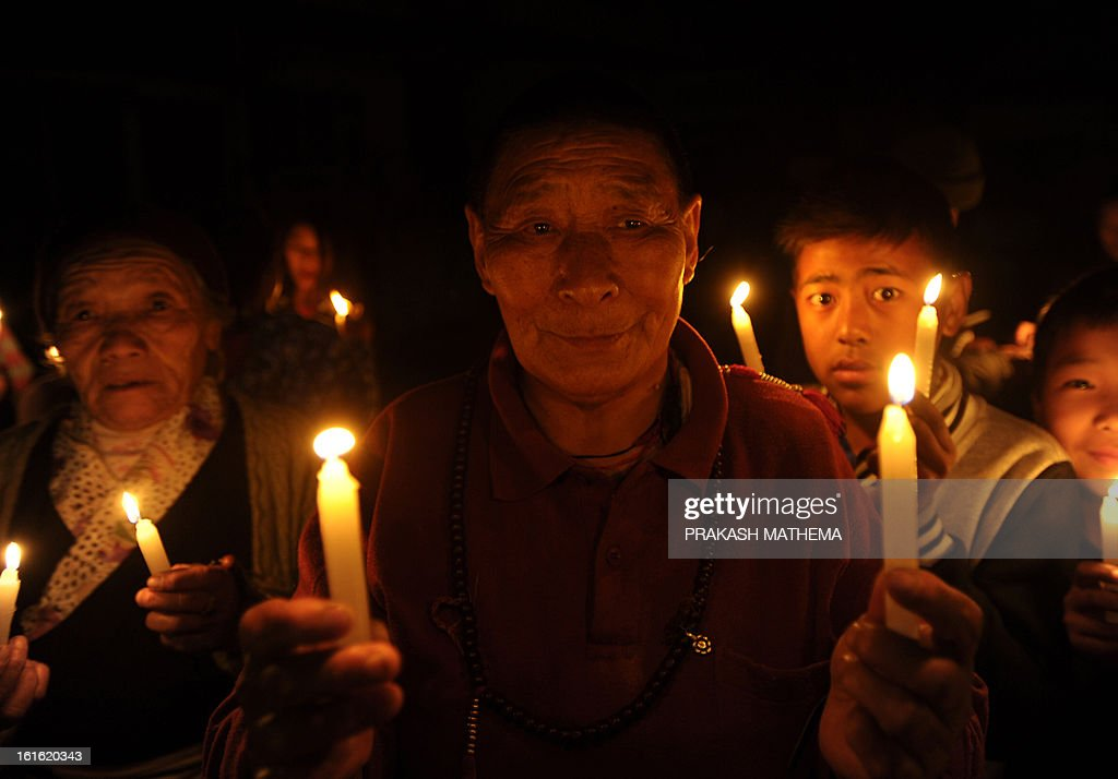 Tibetans-in-exile take part in a candlelight vigil following the self-immolation attempt by a monk earlier today, marking the one hundredth Tibetan to self immolate in protest against Chinese rule in Tibet, in Kathmandu on February 13, 2013. A Tibetan exile turned himself into a ball of fire in front of a Buddhist monument Wednesday, the 100th self-immolation attempt since 2009 in a wave of protests against Chinese rule. AFP PHOTO/Prakash MATHEMA