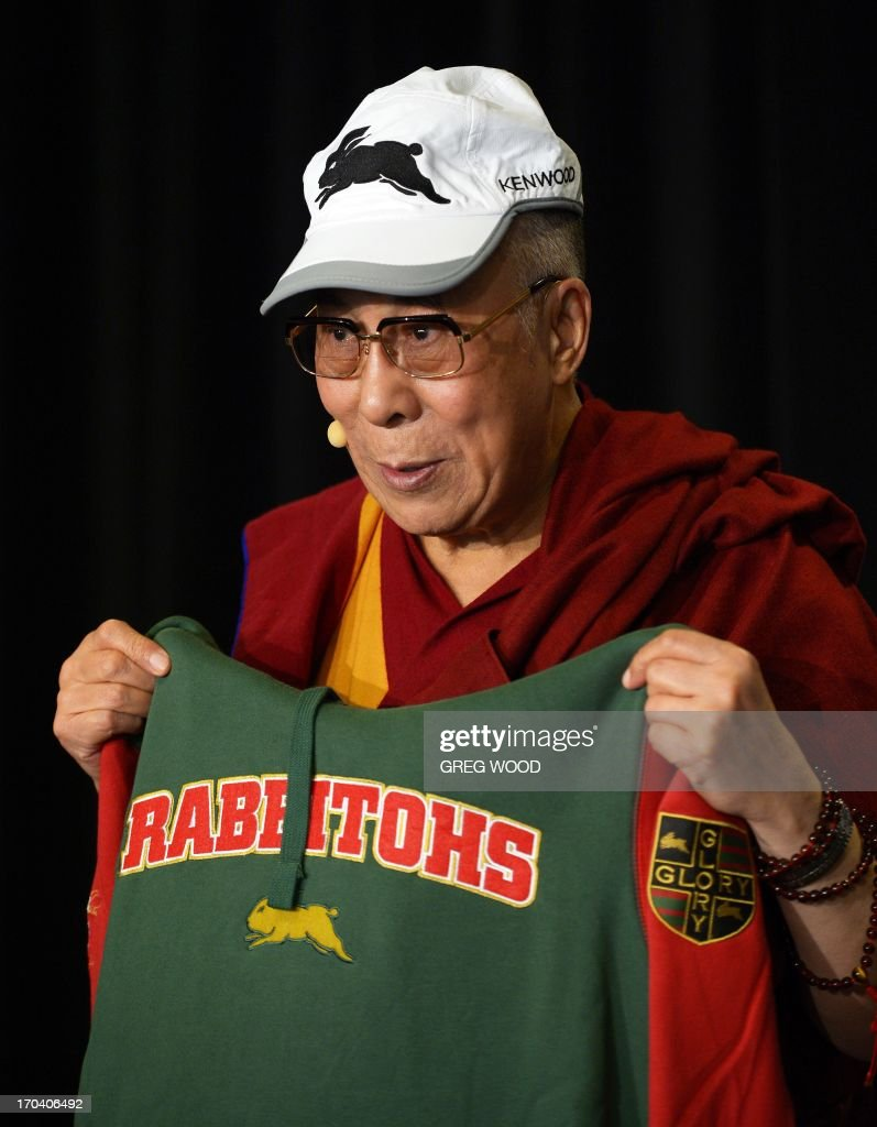 Tibet's exiled spiritual leader the Dalai Lama holds a South Sydney Rabbitohs rugby league team jersey and wears a club cap during a press conference in Sydney on June 13, 2013. The Dalai Lama is on a national tour to Australia for ten days with events throughout the visit carrying the message 'Beyond Religion; Ethics for a Whole World'. AFP PHOTO / Greg WOOD