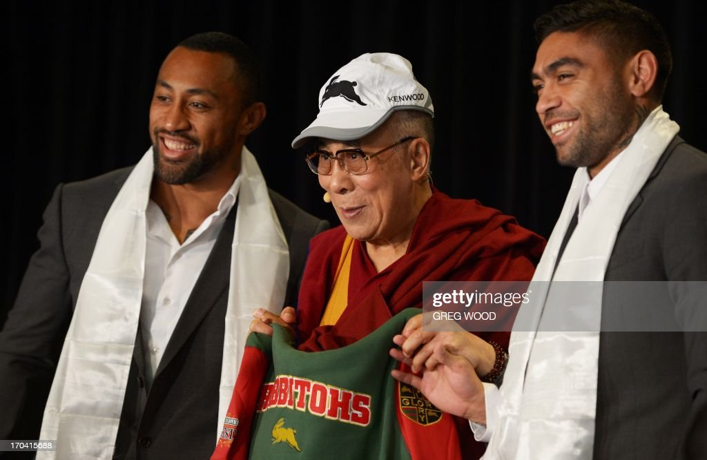 Tibet's exiled spiritual leader the Dalai Lama (C) holds a South Sydney Rabbitohs rugby league team jersey and wears a club cap as he poses alongside players Nathan Merritt (R) and Roy Asotasi (L) following a presentation during a press conference in Sydney on June 13, 2013. The Dalai Lama is on a national tour to Australia for ten days with events throughout the visit carrying the message 'Beyond Religion; Ethics for a Whole World'. AFP PHOTO / Greg WOOD