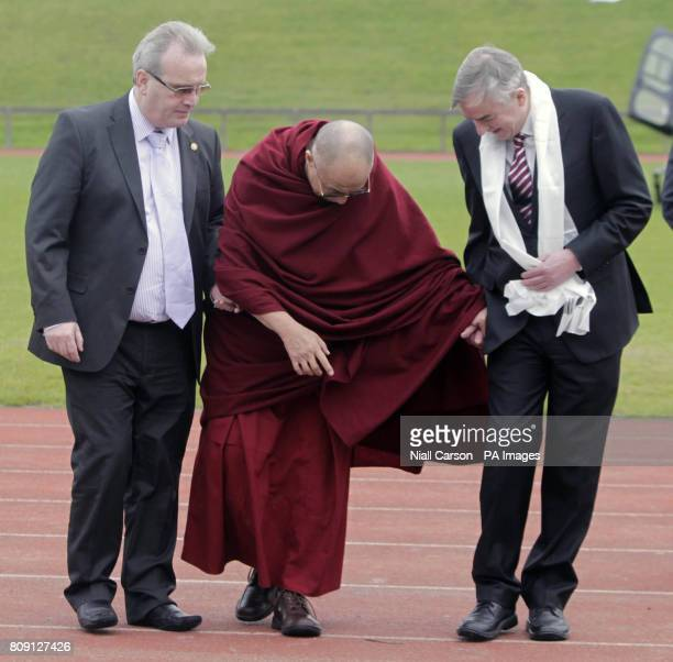Tibet's spiritual leader the Dalai Lama pauses to avoid treading on an earthworm on his way to an address at the University of Limerick on 'the Power...