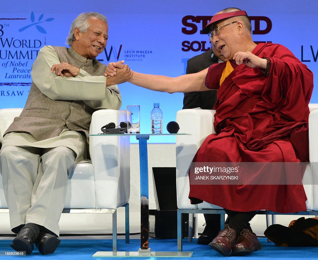 Tibet's spiritual leader the Dalai Lama (R) shakes hands with Muhammad Yunus, Bangladeshi banker and 2006 Nobel Peace Prize Laureate at the end of the World Summit of Nobel Peace Laureates on October 23, 2013 in Warsaw. Warsaw host Nobel Peace Laureates and representatives of organisations interested in peace promotion from all over the world. The summit takes place from October 21-23 under the theme Stand in Solidarity for Peace - Time to Act'. AFP PHOTO / JANEK SKARZYNSKI