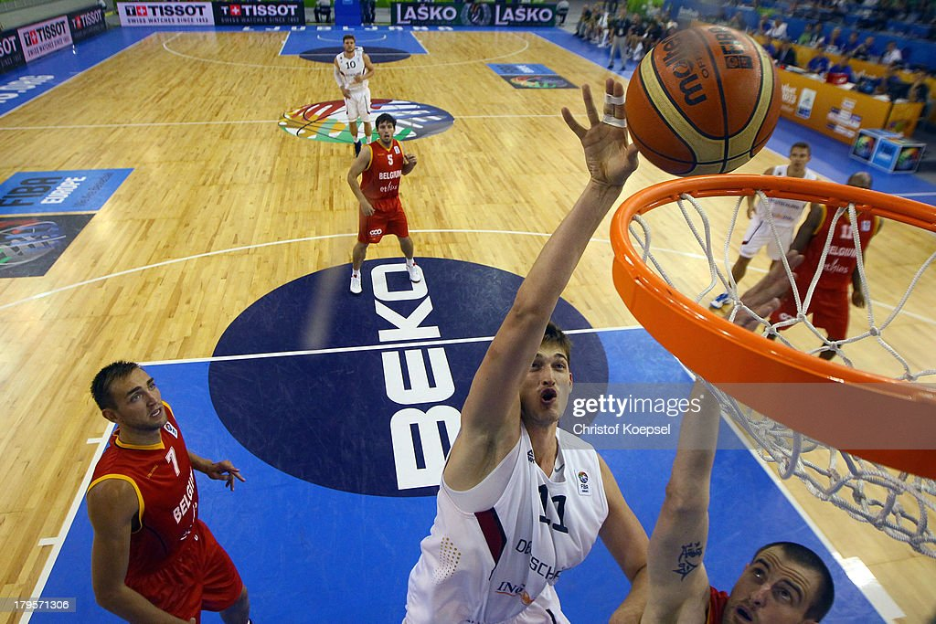 Tibor Pleiss of Gemany (C) dunks the ball against Sacha Massot of Belgium (R) and Axel Hervelle of Belgium (L) during the FIBA European Championships 2013 first round group A match between Germany and Belgium at Tivoli Arena on September 5, 2013 in Ljubljana, Slovenia.