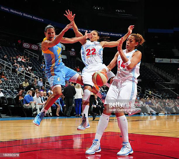 Ticha Penicheiro of the Chicago Sky drives to the basket against Armintie Price and Erika deSouza of the Atlanta Dream at Philips Arena on August 22...