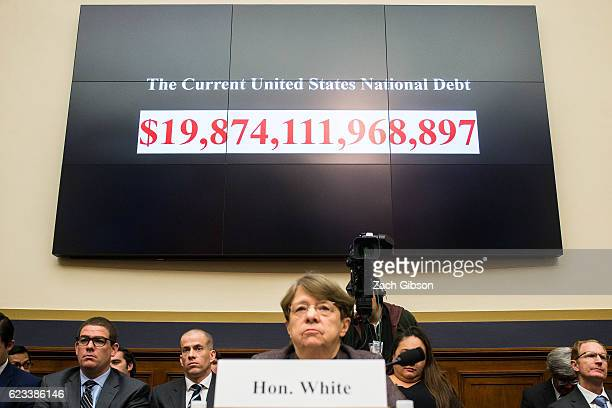A ticker showing the increasing United States National Debt is shown behind SEC Chairman Mary Jo White during a House Financial Services Committee...