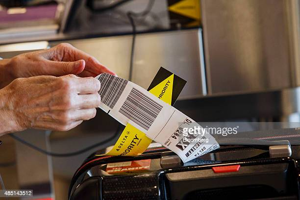 A ticket agent attaches a Sky Priority baggage tag before it is placed on a conveyor belt in Delta Air Lines Inc Terminal 5 at Los Angeles...