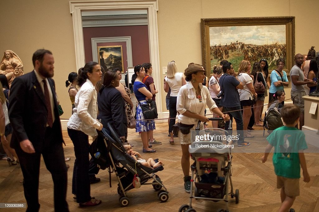 Ticket holders to the 'Alexander McQueen: Savage Beauty' exhibit stand in line at the Metropolitan Museum of Art July 31, 2011 in the Manhattan borough of New York. The exhibit, which closes August 7, will be one of the museum's most popular exhibits. McQueen, who committed suicide in 2010, was considered one of the greatest fashion designers of his generation.
