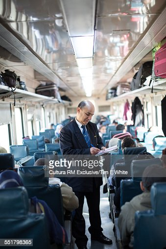 Ticket inspector and passengers in train carriage, Tunisia