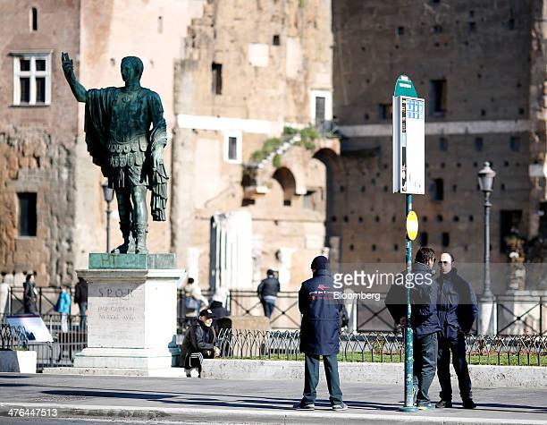 Ticket inspectors stand by a bus stop in front of the remains of the Roman Forum in Rome Italy on Monday March 3 2014 Italian Prime Minister Matteo...