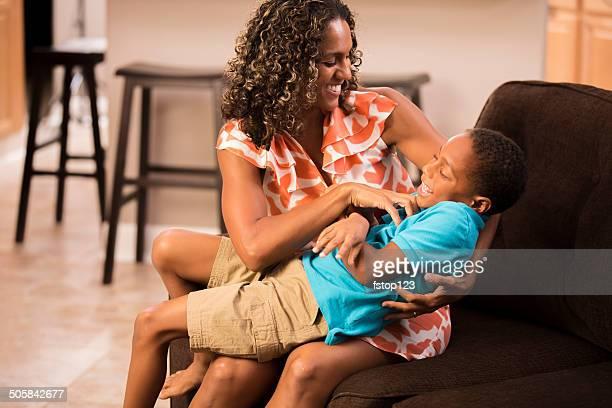 Verwöhnen Sie mich! Lachender kleiner Junge mit seiner Mutter tickled.  Wie zu Hause fühlen.