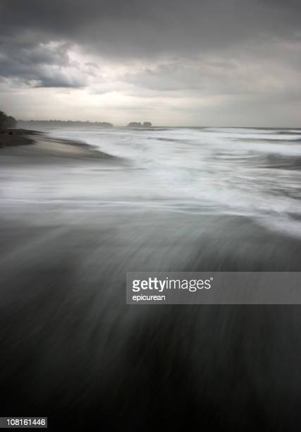 Tide on Black Sand Beach Shore with Storm Clouds Above
