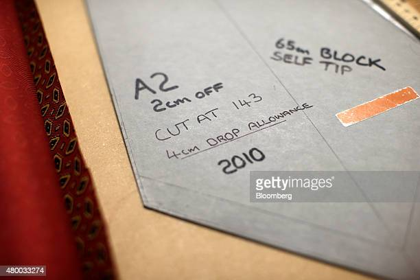Tie dimension information sits on a fabric template at Drake's factory outlet store in London UK on Friday June 26 2015 Consumer confidence in the UK...