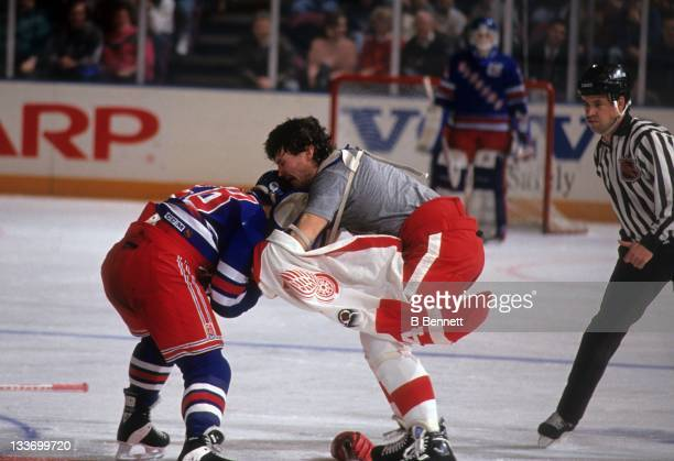 Tie Domi of the New York Rangers fights with Bob Probert of the Detroit Red Wings on February 9 1992 at the Madison Square Garden in New York New York