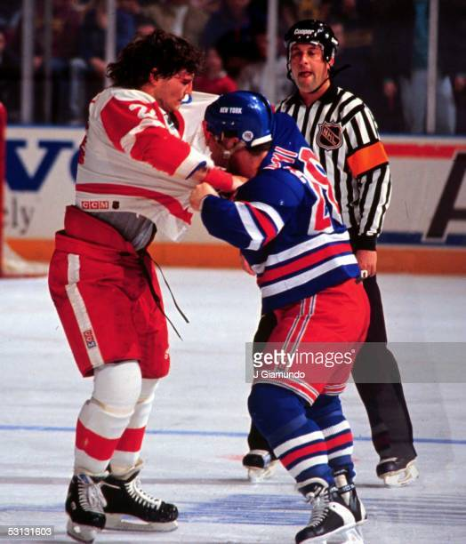 Tie Domi of the New York Rangers fights with Bob Probert of the Detroit Red Wings on February 2 1992 at the Madison Square Garden in New York New York