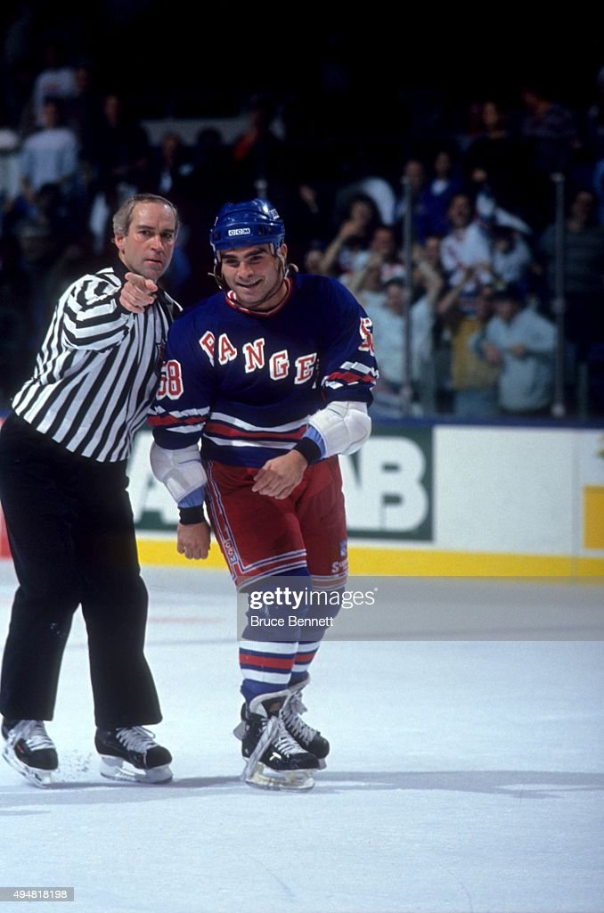 Tie Domi #68 of the New York Rangers is escorted to the penalty box after a fight during an NHL preseason game against the New York Islanders in September, 1990 at the Nassau Coliseum in Uniondale, New York.