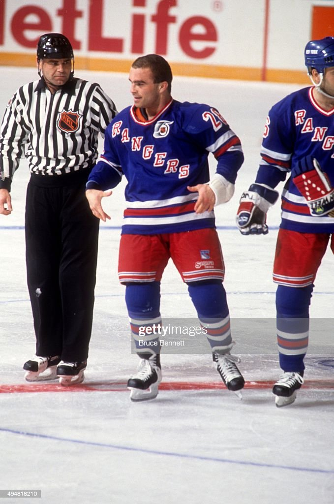 Tie Domi #28 of the New York Rangers is escorted to the penalty box after a fight during an NHL game against the Detroit Red Wings on February 9, 1992 at the Madison Square Garden in New York, New York.
