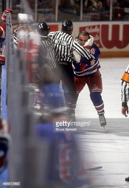 Tie Domi of the New York Rangers is held back by linesman Randy Mitton as Domi tries to get at Bob Probert of the Detroit Red Wings on February 9...