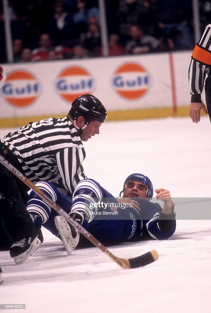 Tie Domi #28 of the Toronto Maple Leafs lays on the ice as a linesman holds him down after a fight against the New Jersey Devils on January 31, 1997 at the Continental Airlines Arena in East Rutherford, New Jersey.