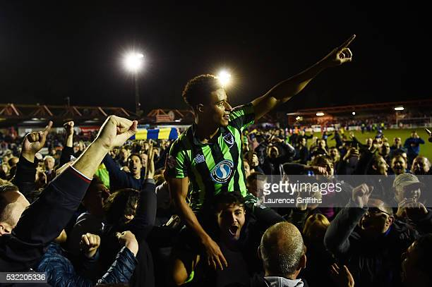 Tie winning goalscorer Lyle Taylor of AFC Wimbledon is carried aloft by the fans after their team wins promotion to League One during the Sky Bet...