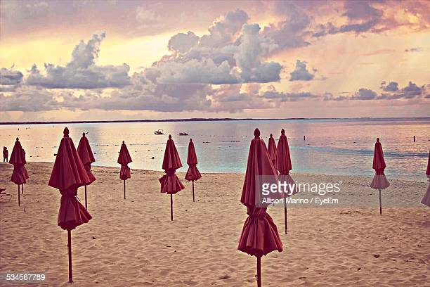 Tied Parasols On Beach Against Cloudy Sky