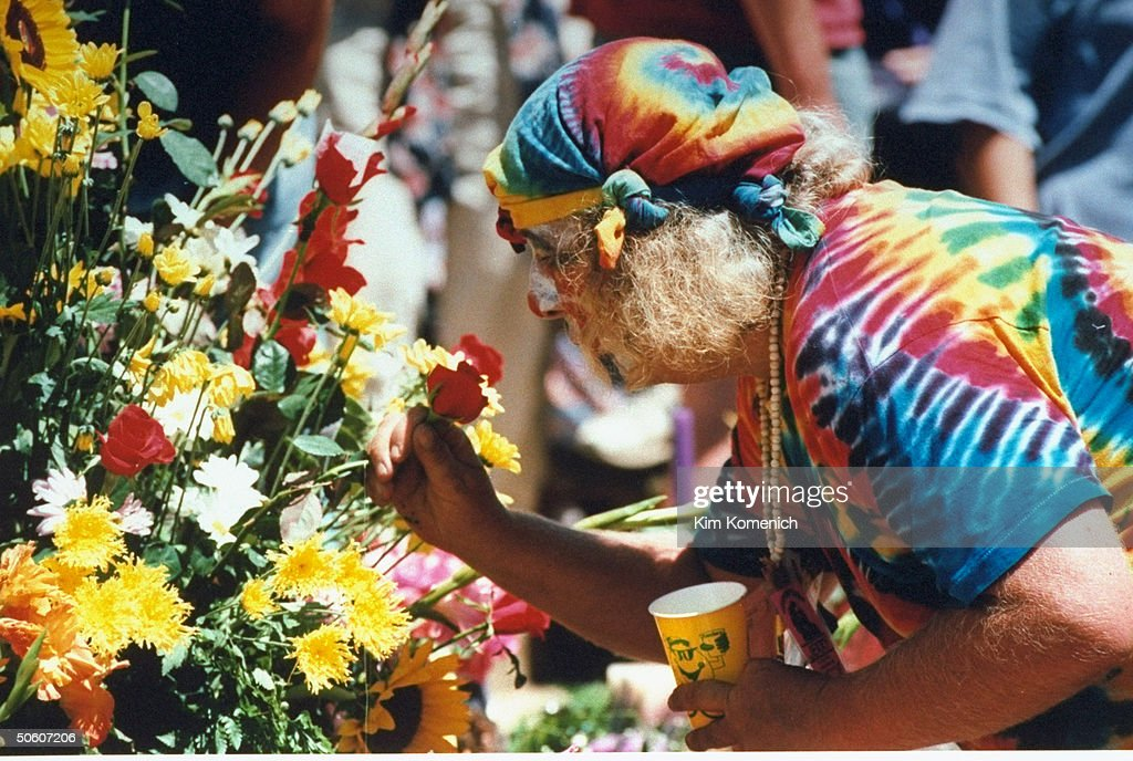 Tie-dye-clad hippie icon Hugh Wavy Gravy Romney leaning over to smell boquet of flowers during memorial service for Grateful Dead front-man Jerry Garcia at Golden Gate Park.