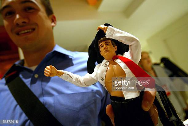 Tien Vominh holds up a custom tailored new Donald Trump 12inch talking doll September 29 2004 at the Toys 'R' Us store in New York City The doll's...