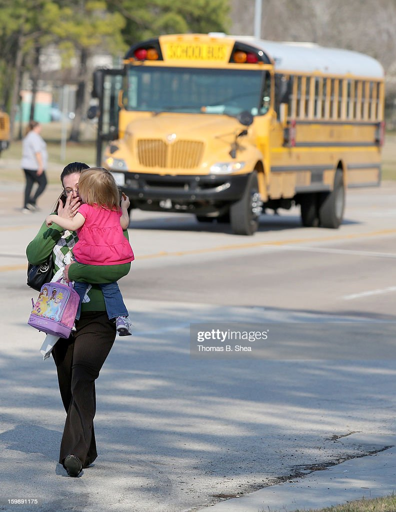 Tierna Tate carries her 19th month old daughter Olivia Tate after she picked her up for the Lone Star College Daycare on January 22, 2013 in The Woodlands, Texas. According to reports, three people were injured during a shooting on the courtyard between the Library and cafeteria.