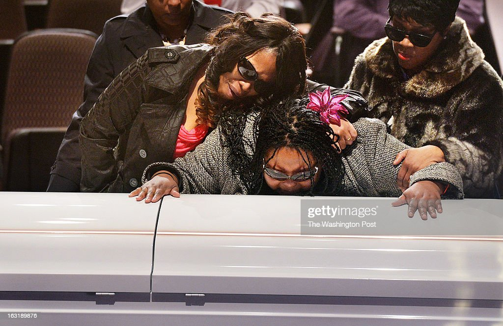 Tiffanee Price, left, mourns with Teresa Myles-Price, center, and Barbara Cromer, right, at a memorial service for Darrell Price Jr. and his daughters, Patrice Price, Tania Price, and Daijah Price at First Baptist Church of Glenarden on Monday March 04, 2013 in Upper Marlboro, MD. The four died as a result of a house fire last month. Tiffanee is the sister to Darrell while Teresa is Darrell's wife and the mother to Patrice, Tania, and Daijah. Barbara is Darrell's aunt. They were mourning over the casket containing the remains of Daijah and Tania while another casket contained the remains of Darrell and Patrice.