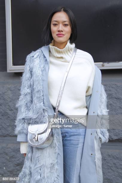 Tiffany Hsu is seen at Spring Studios outside the Phillip Lim show wearing three quarter length pastel blue faux fur coat denim jeans with frayed hem...