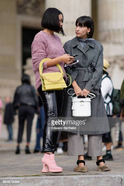 Tiffany Hsu wears a pink pull over a yellow bag black pvc pants pink shoes outside Margiela during Paris Fashion Week Womenswear Spring/Summer 2018...