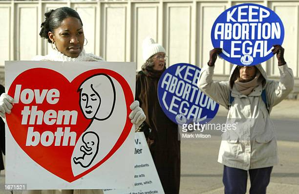 Tiffany Keeler holds a sign reading 'Love them both' as people hold 'Keep Abortion Legal' signs during a protest in front of the US Supreme Court...
