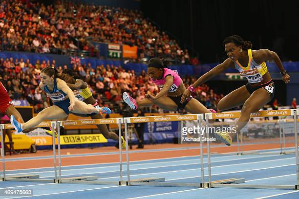 Tiffany Porter of Great Britain clears the final hurdle alongside eventual winner Nadne Hildebrand of Germany and Kellie Wells of USA during the...