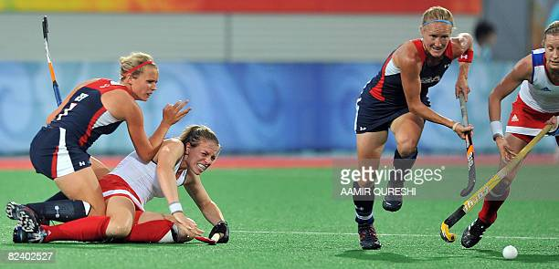 Tiffany Snow of The US runs as her teammate Lauren Crandall and Kate Walsh of Great Britain fall on the ground during their 2008 Beijing Olympic...