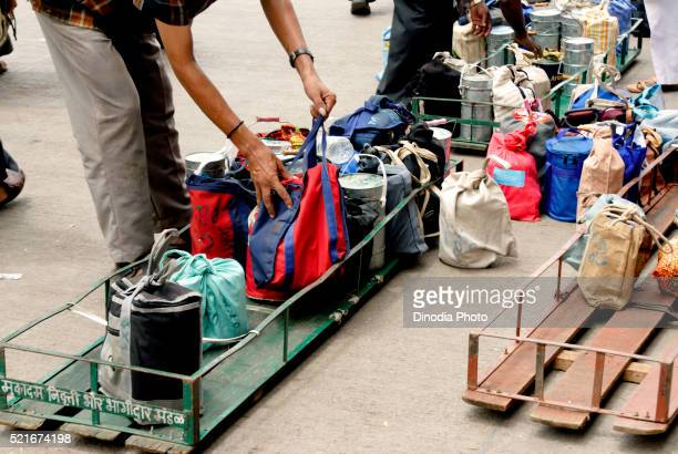 Tiffinwala or dabbawala arranging lunchboxes in crate, Bombay Mumbai, Maharashtra, India