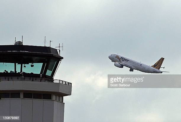 Tiger Airways flight to Sydney takes off past a Air Traffic Control Tower on August 12 2011 in Melbourne Australia Tiger Airways resumed flights...