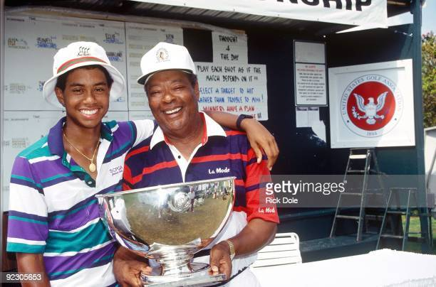 Tiger Woods age 15 years six months and 28 days and father Earl Woods pose for a photo while celebrating Tiger's victory at the 1991 USGA Junior...