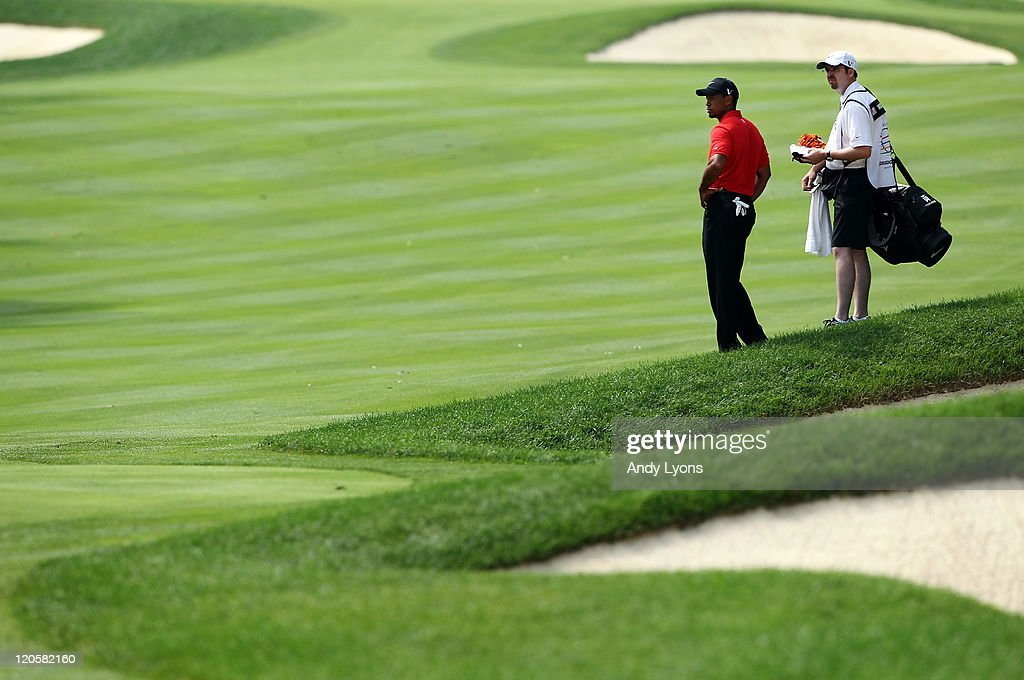 <a gi-track='captionPersonalityLinkClicked' href=/galleries/search?phrase=Tiger+Woods&family=editorial&specificpeople=157537 ng-click='$event.stopPropagation()'>Tiger Woods</a> (L) and caddie Bryon Bell (R) look on from the second hole fairway during the final round of the World Golf Championships-Bridgestone Invitational on the South Course at Firestone Country Club on August 7, 2011 in Akron, Ohio.