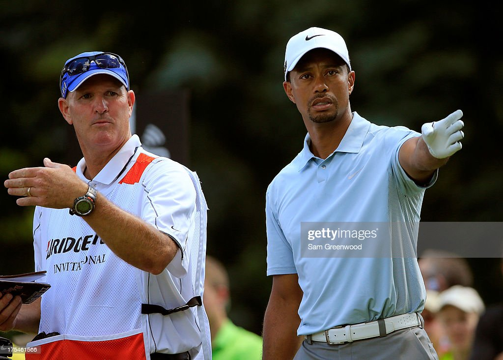 Tiger Woods (R) and his caddie Joe LaCava discuss a shot on the sixth tee during the Third Round of the World Golf Championships-Bridgestone Invitational at Firestone Country Club South Course on August 3, 2013 in Akron, Ohio.