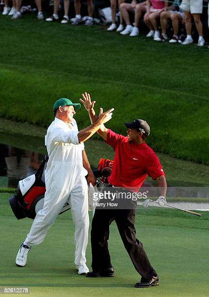 Tiger Woods and his caddie Steve Williams celebrate after Woods chipped in for birdie on the 16th hole during the final round of The Masters at the...