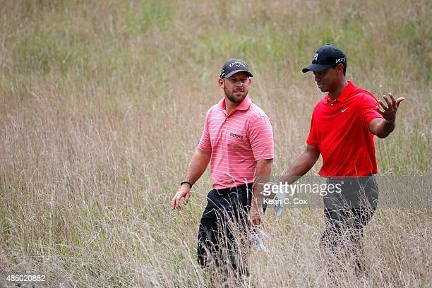 Tiger Woods and Scott Brown walk the fairway on the fifth hole during the final round of the Wyndham Championship at Sedgefield Country Club on...