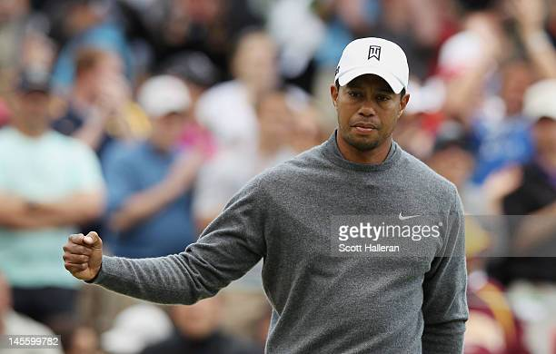 Tiger Woods celebrates a birdie putt on the first hole during the third round of the Memorial Tournament presented by Nationwide Insurance at...