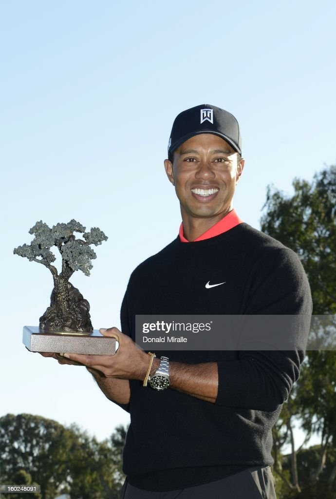 Tiger Woods celebrates his -14 under win with the winner's trophy during the Final Round at the Farmers Insurance Open at Torrey Pines Golf Course on January 28, 2013 in La Jolla, California.