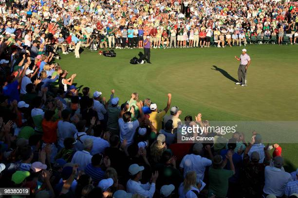 Tiger Woods celebrates making birdie on the 18th hole in front of a gallery of fans during the third round of the 2010 Masters Tournament at Augusta...