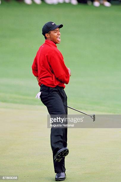 Tiger Woods celebrates on the 18th hole after winning the 1997 Masters Tournament at Augusta National Golf Club on April 13 1997 in Augusta Georgia