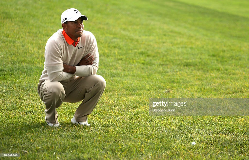 Tiger Woods checks out his shot out of the rough on the 15th hole during the first round of the Farmers Insurance Open on the South Course at Torrey Pines Golf Course on January 24, 2013 in La Jolla, California.