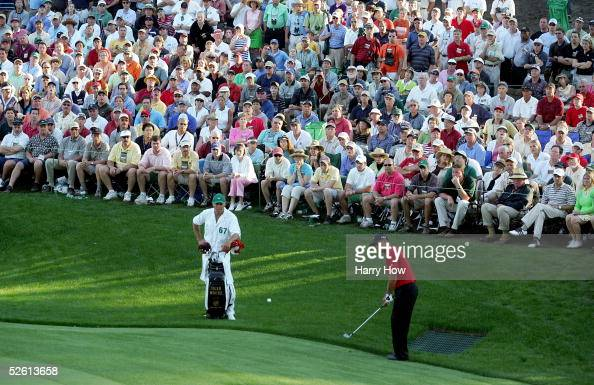 Tiger Woods chips a shot to the 16th green for birdie as his caddie Steve Williams looks on during the final round of The Masters at the Augusta...