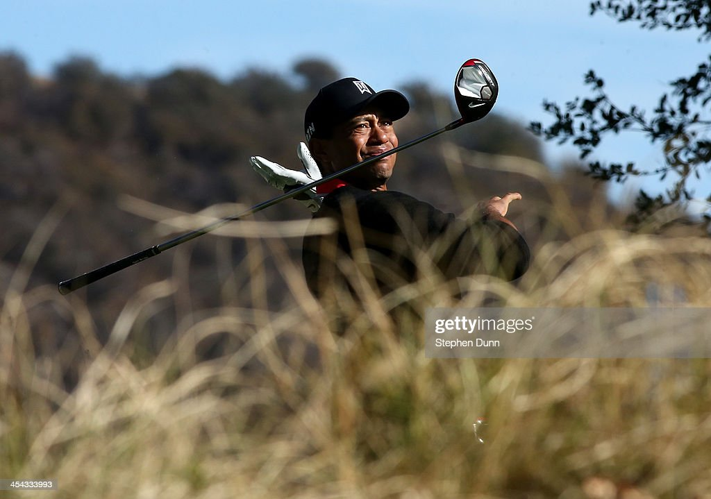 Tiger Woods drops his club after hitting his tee shot on the 11th hole during the final round of the Northwestern Mutual World Challenge at Sherwood Country Club on December 8, 2013 in Thousand Oaks, California.