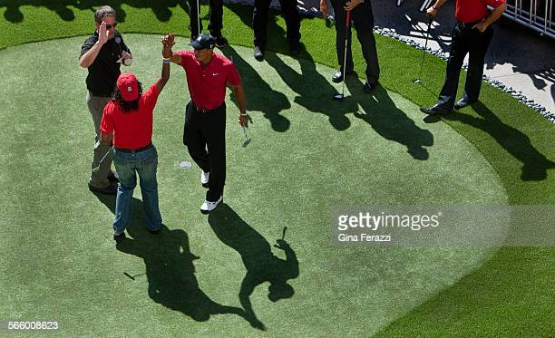 Tiger Woods high–fives contestant Carol Alexander after she sank a putt from off the green during a putting challenge with local fans on a custom...